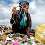 woman picking up plastic trash washed up on beach
