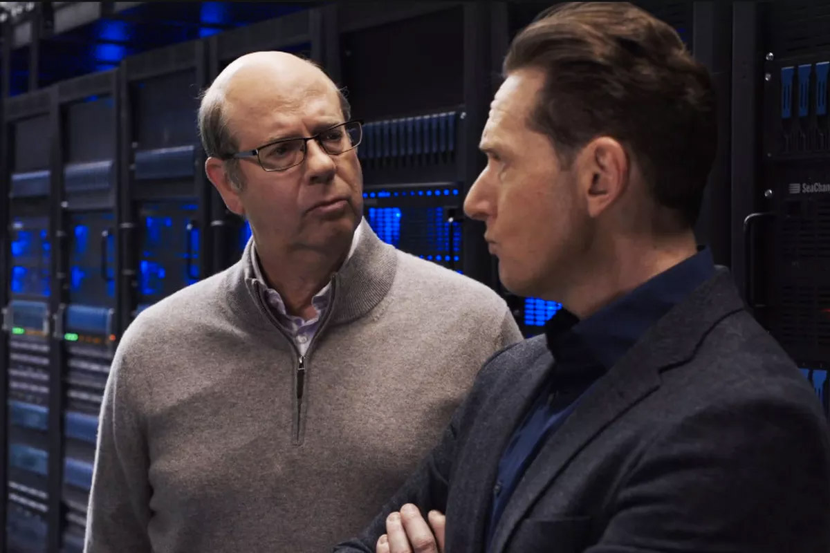 Silicon Valley actors conversing in cold aisle containment area of large data center
