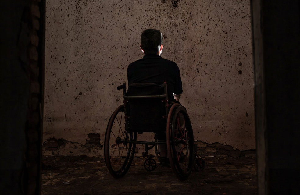 disabled man in wheelchair, sitting in the dark